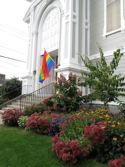 Main Street entrance to church with rainbow flag.