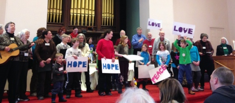 Youth and choir sing and hold signs (Hope, Love, Peace) while Paula Gills plays guitar