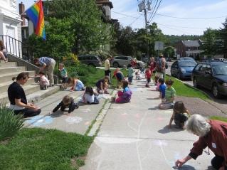 children and teachers draw chalk flowers on sidewalk outside the church