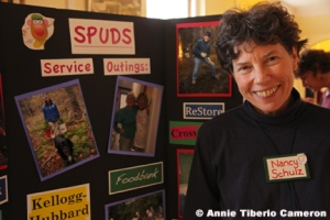Nancy Schulz stands with a SPUDS display board in the Vestry